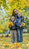 Mère étreignant deux enfants parmi l'automne photographie stock libre de droits