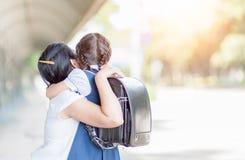 Mère étreignant la fille dans l'étudiant uniforme Images stock