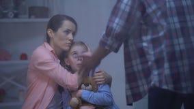 Mère étreignant la fille, se protégeant contre le père fâché le jour pluvieux, harcèlement clips vidéos