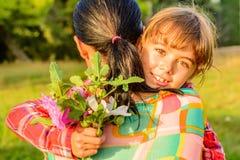 Mère étreignant sa fille avec des fleurs image stock