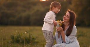 Mère étreignant ses deux fils dans le coucher du soleil dans le domaine Maman heureuse aimante d'enfants clips vidéos
