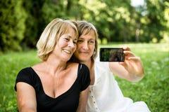 Mère aînée avec l'enfant prenant la photo Photographie stock libre de droits
