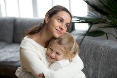 Mère affectueuse étreignant la petite fille montrant l'amour, le soin et la petite gorgée Photos stock
