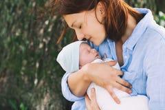 Mère affectueuse avec son bébé nouveau-né sur ses bras Photos stock