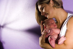 Mère affectueuse berçant la chéri nouveau-née Photographie stock libre de droits