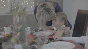 Mère affectueuse embrassant la petite fille mignonne s'asseyant sur la table de dîner célébrant Noël en belle atmosphère conforta banque de vidéos