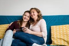 Mère affectueuse et fille s'asseyant sur le sofa à la maison Images stock