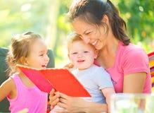 Mère affichant un livre à ses enfants Photos libres de droits