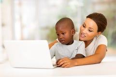 Mère africaine d'ordinateur portable de garçon Images libres de droits