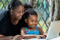 Mère africaine et enfant regardant l'ordinateur portable dehors Photographie stock