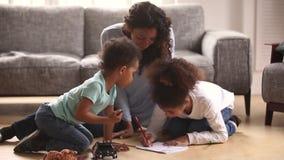 Mère africaine et petits enfants s'asseyant sur le dessin chaud de planchers banque de vidéos