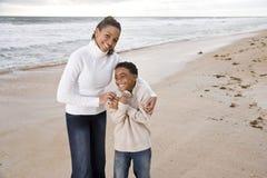 Mère afro-américaine et fils à la plage photo libre de droits