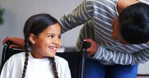 Mère agissant l'un sur l'autre avec la fille dans le fauteuil roulant banque de vidéos