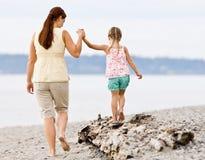 Mère aidant le descendant à marcher sur le logarithme naturel à la plage image libre de droits