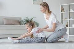 mère aidant sa fille à faire la courbure en avant Image libre de droits