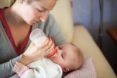 Mère alimentant la chéri infantile Image libre de droits