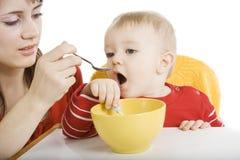 Mère alimentant sa chéri Photos stock