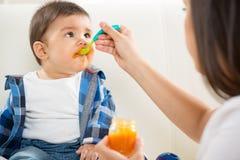 Mère alimentant sa chéri Image stock
