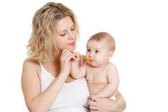 Mère alimentant sa chéri par la cuillère Photo stock