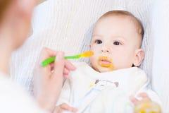 Mère alimentant son beau bébé garçon avec la cuillère Photo stock
