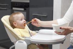Mère alimentant son fils Image stock
