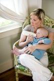 Mère allaitant au biberon sa vieille chéri de sept mois Image stock
