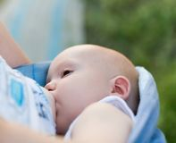 Mère allaitant au sein son enfant en bas âge dans l'élingue Photos libres de droits