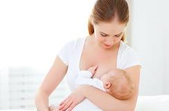 Mère allaitant le bébé nouveau-né dans le lit blanc photos libres de droits