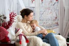 Mère allaitant son fils d'enfant en bas âge s'asseyant dans le fauteuil confortable, hiver images stock