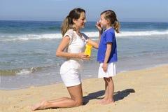 Mère appliquant la protection solaire Images stock