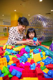 Mère asiatique et fille chinoises jouant des blocs au terrain de jeu Images stock