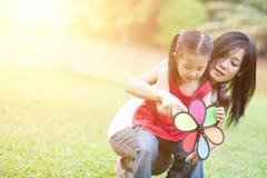 Mère asiatique et fille jouant le moulin à vent à dehors Photos libres de droits