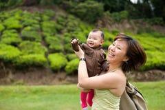 Mère asiatique jouant avec son bébé de 7 mois Image stock