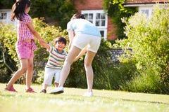 Mère asiatique jouant dans le jardin d'été avec des enfants image libre de droits