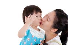 Mère asiatique portant et se bécotant sa fille sur le backgr blanc Image stock