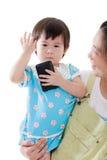 Mère asiatique portant sa fille sur le fond blanc Photographie stock libre de droits