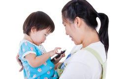 Mère asiatique portant sa fille sur le fond blanc d'isolement Image libre de droits