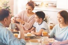 Mère attentive préparant le thé savoureux pour tout le monde Photo stock