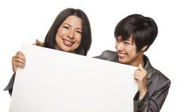 Mère attirante et fille de métis tenant le blanc vide SI Photographie stock libre de droits