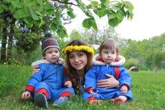 Mère avec de jeunes jumeaux s'asseyant sur un pré vert dans le sprin tôt Images libres de droits