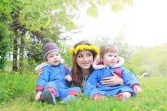 Mère avec de jeunes jumeaux s'asseyant sur un pré vert dans le sprin tôt Photos libres de droits