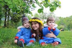 Mère avec de jeunes jumeaux s'asseyant sur un pré vert dans le sprin tôt Photo stock