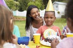 Mère avec des enfants appréciant la fête d'anniversaire extérieure ensemble Image libre de droits