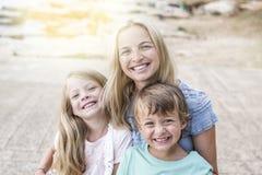 Mère avec des enfants caressant sur la plage Photographie stock libre de droits