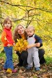Mère avec des enfants en stationnement d'automne Photographie stock libre de droits