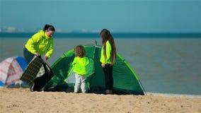 Mère avec des enfants préparant une tente sur la plage pour des familles banque de vidéos