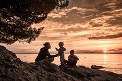 Mère avec des enfants s'asseyant sur la plage, parler et jouer Photo libre de droits