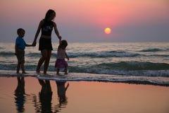 Mère avec des enfants sur le coucher du soleil Images stock