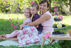 Mère avec deux enfants étreignant au pique-nique d'été photo libre de droits