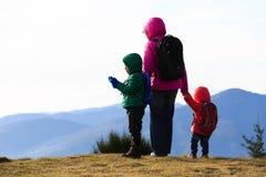 Mère avec deux enfants trimardant en montagnes Image libre de droits
